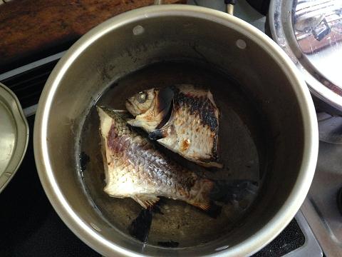 酒、酢、水を入れた鍋にフナを入れる