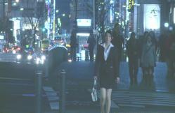 夜の街をスーツ姿で歩く由佳