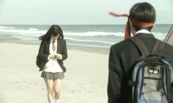 海辺でメールを打ちながら歩いている紗英に近づく矢部