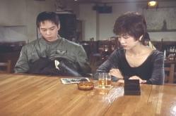 テーブルに撮った写真を真理にを出した西田