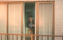 妙子の部屋にあった望遠鏡で向こうを見る水上
