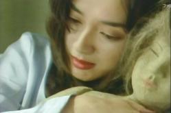 何かに怯えながら、人形を抱いている女