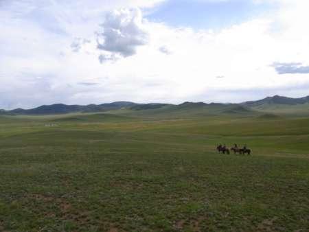 草原を馬で行く