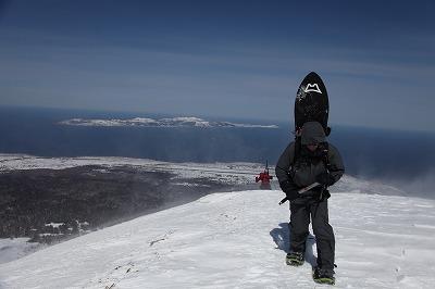 海をバックに利尻岳をハイクするアシスタントの本村さん。