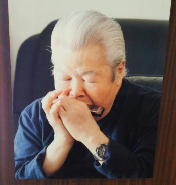 パネル・ハモニカを吹く山岸一雄さん(25.6.30)