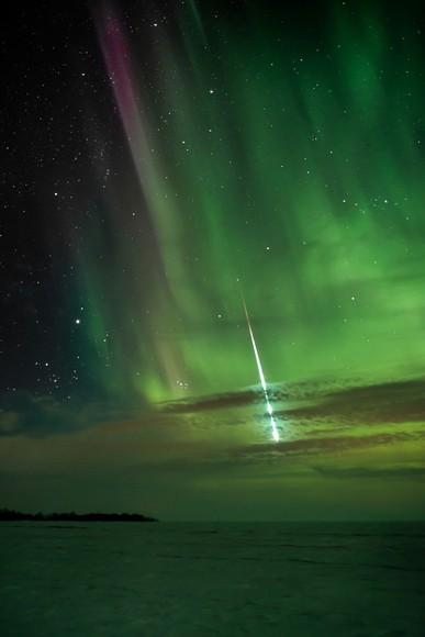 オーロラの夜空と流星。カナダ、マニトバ州パトリシア・ビーチの氷に覆われた湖面。