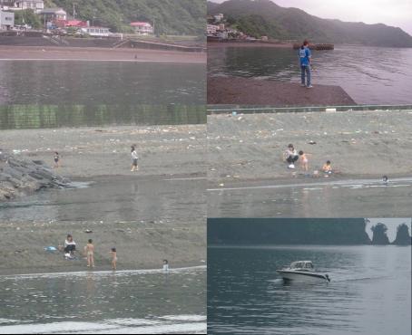 伊東市川奈の川奈東防波堤灯台の釣り場から見れた砂浜で遊ぶ幼い子供達と走り去るモーターボートの写真