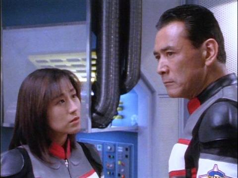 なぜアスカ隊員かヒビキ隊長に尋ねるユミムラ・リョウ隊員(演:斉藤りさ)