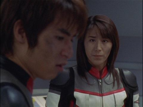 返答に困るアスカ隊員を見守るユミムラ・リョウ隊員(演:斉藤りさ)