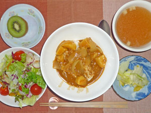 薬膳カレーライス(高きび入り),漬物,サラダ,コンソメスープ,キウイフルーツ