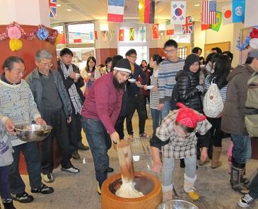 楽しい餅つきに留学生も参加、額に汗も・・・